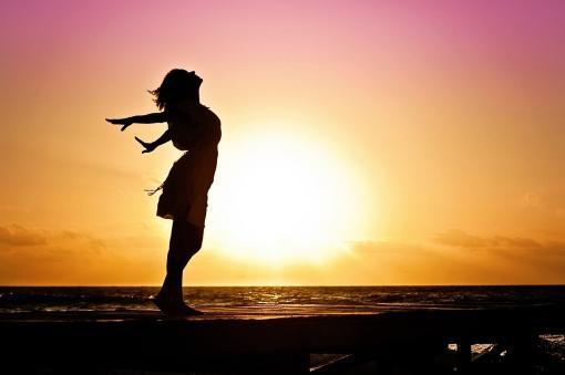 Ombre d'une femme heureuse au coucher de soleil