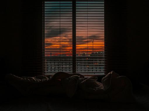 Chambre dans le noir avec vue sur coucher de soleil