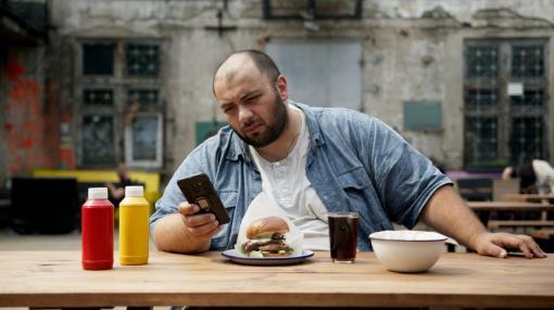 Homme en surpoids qui mange