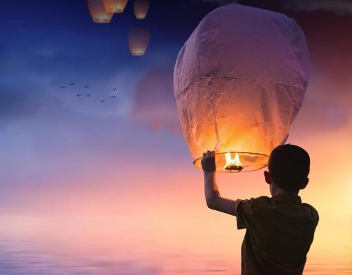 Un enfant lâche un ballon dans les airs pour accompagner les morts