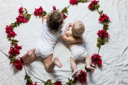 2 Bébés qui allongés sur le ventre entouré d'un cœur de fleurs