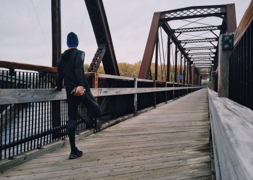 Homme qui s'étire sur un pont, après avoir couru
