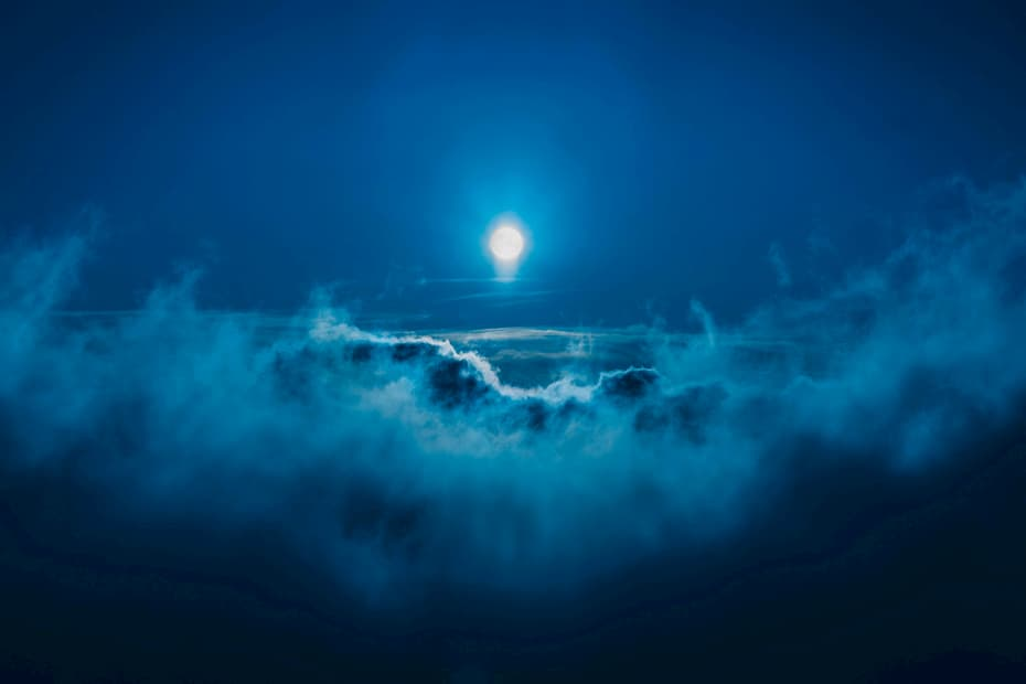 Lune de minuit flottant sur un ciel nuageux.