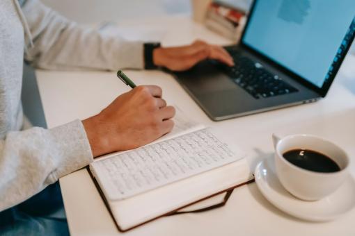 Travailler sur son ordinateur avec un bloc note à côte et un café