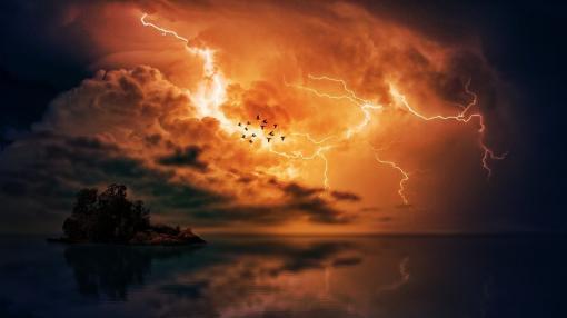 Puissant orage orange de nuit avec une volées d'oiseaux
