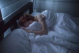Femme qui dort dans son lit.