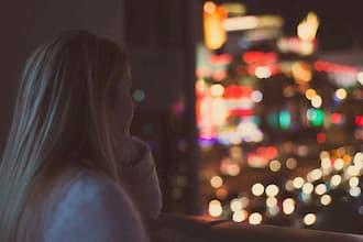 Femme de dos qui regarde les lumières de la ville